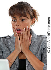Open-mouthed woman in front of laptop