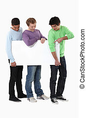 Three young lads with a blank board