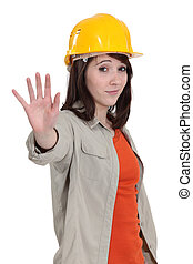 A female construction worker doing a stop sign.