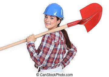 Woman holding shovel over shoulder