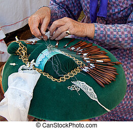 Hands making  bobbin lace