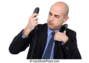 Overwhelmed businessman answering telephones