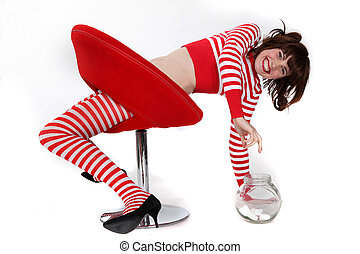 young woman in red and white striped clothes trying to reach a jar full with bonbons