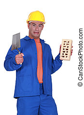 mason holding a trowel and a brick and looking disgusted