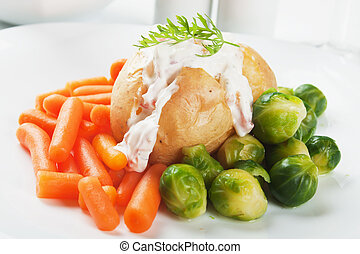 Jacket potato with cream sauce, baby carrot and brussels...