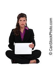Brunette businesswoman sat cross-legged on the floor