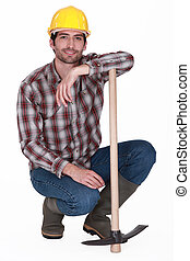 handsome bricklayer with arm resting on pickaxe