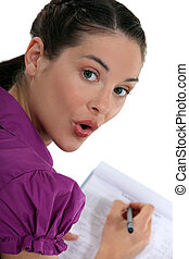 Woman writing on a clipboard