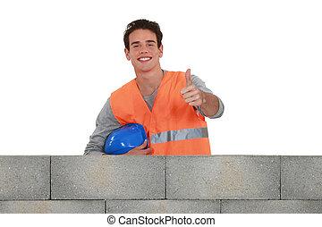 Positive mason stood by wall
