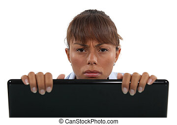 Displeased businesswoman peering over laptop