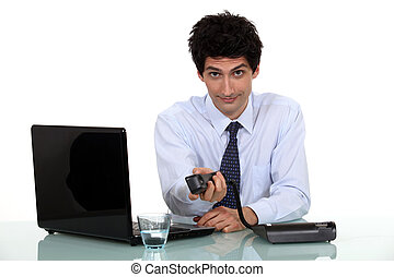 portrait of handsome businessman working on laptop holding...