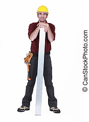 portrait of young carpenter posing with hands resting on steel plank