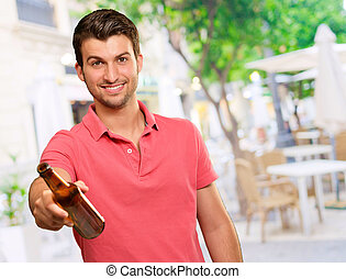 young man holding a beer