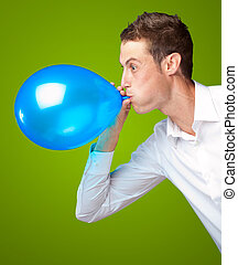 Portrait Of Young Man Blowing A Balloon Isolated On Green...