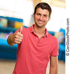 young man smiling with thumbs up, indoor