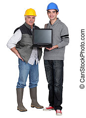 Two manual worker with a laptop.
