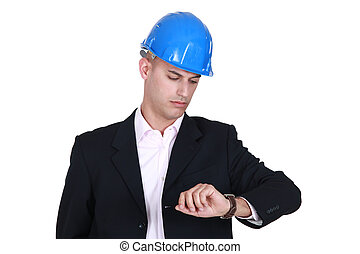 Suited man in a hardhat looking at his watch