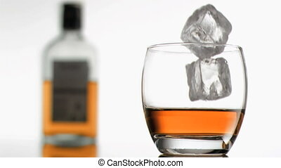 Ice cubes in super slow motion falling in a glass of whiskey...