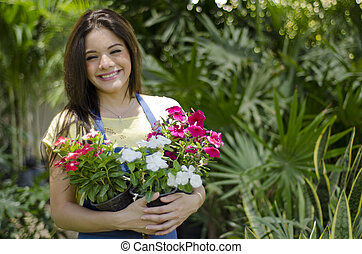 Cute gardener carrying some flowers - Happy female gardener...