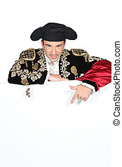 Man in a matador costume with a board blank for text or...