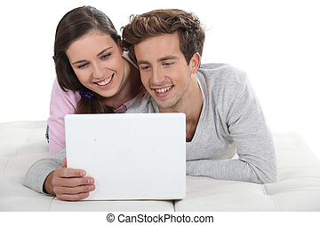 Young couple in front of their laptop