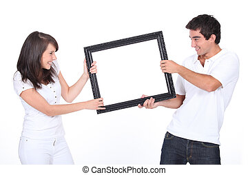 Couple fighting over blank picture frame
