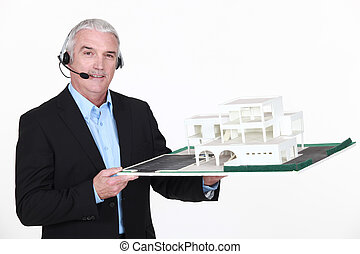 Architect holding replica of housing project