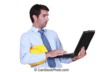 Confused architect looking blankly at laptop