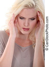 Blond woman suffering from head ache