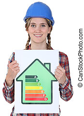 Smiling tradeswoman holding up an energy efficiency rating chart