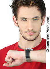 portrait of young man consulting his watch