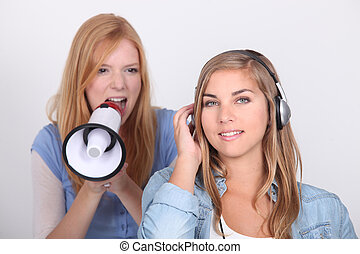 Young girl oblivious to her friend yelling into a megaphone