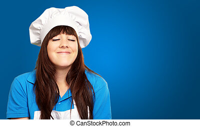 portrait of a young female chef satisfied on blue background