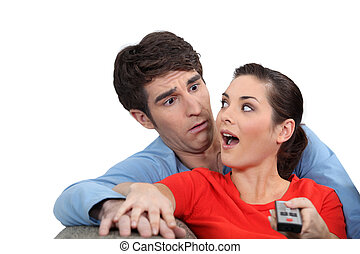Shocked couple with a remote control