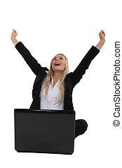 Triumphant businesswoman sitting at a laptop