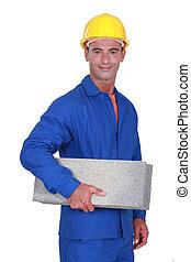 Smiling mason carrying a brick