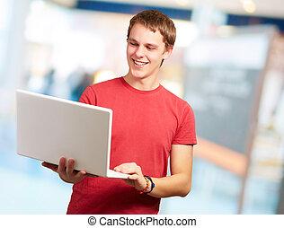 Happy man using laptop, indoor
