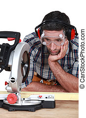 A man staring at a circular saw