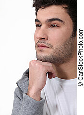 Pensive man stood touching chin with fist