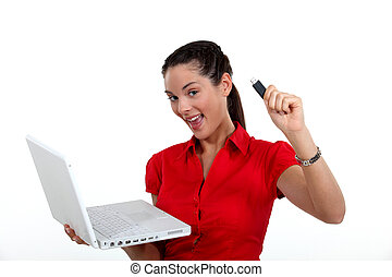 Woman holding laptop and USB key