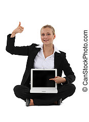 woman holding a laptop and making a thumbs up sign