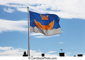 fluttering flag of Helsinki against blue sky