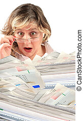 shocking pile of bills - business woman is shocked by the...