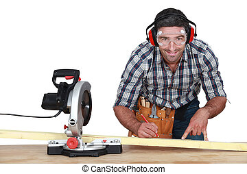 Man with band saw marking wood