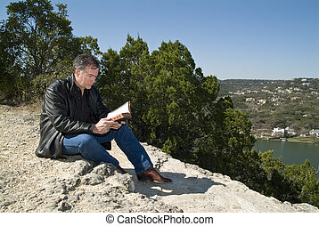 Hilltop Repose - A man sitting on a rocky ledge reading a...
