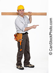 carpenter carrying plank over his shoulder pointing at...