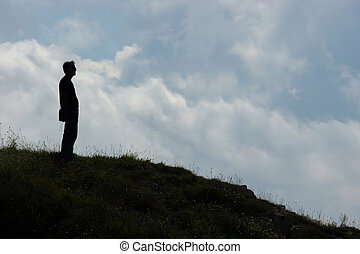 silhouette of a man on a hill