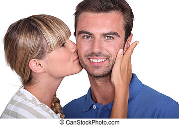 Young woman kissing a mans cheek