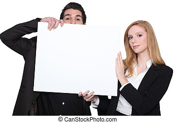 businessman and businesswoman holding an advertising board