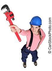 Tradeswoman holding up a pipe wrench